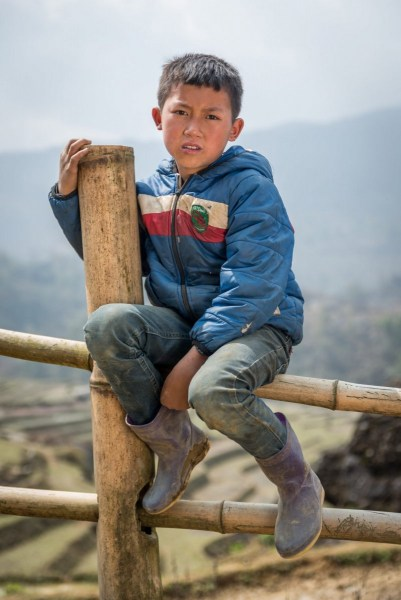 A young farmboy sits on a fence, near Sapa, Vietnam.