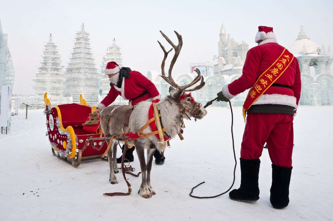 A photo of two men dressed as Santas, with a reindeer, at the Harbin Ice Festival in China.