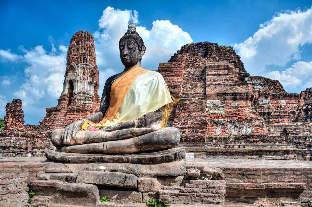 A photo of a Buddha statue wearing a sash in Ayutthaya, Thailand.