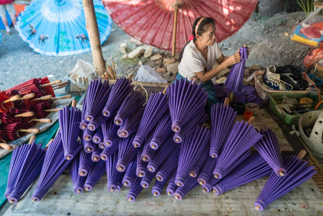 A photo of a woman applying finishing touches to a stack of purple umbrellas, in Bo Sang, Thailand.
