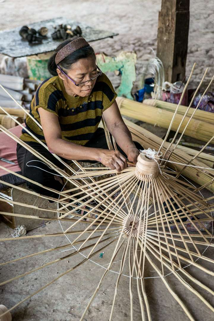 A photo of a woman crafting umbrella ribs in Bo Sang, Thailand.