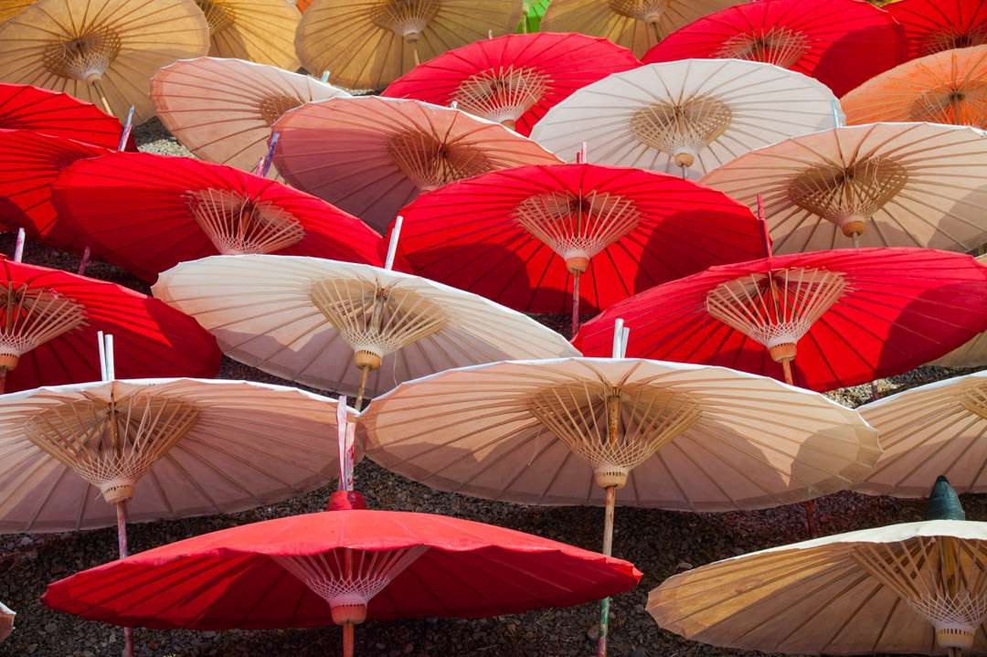A photo of red and white umbrellas drying in the sun, in Thailand.